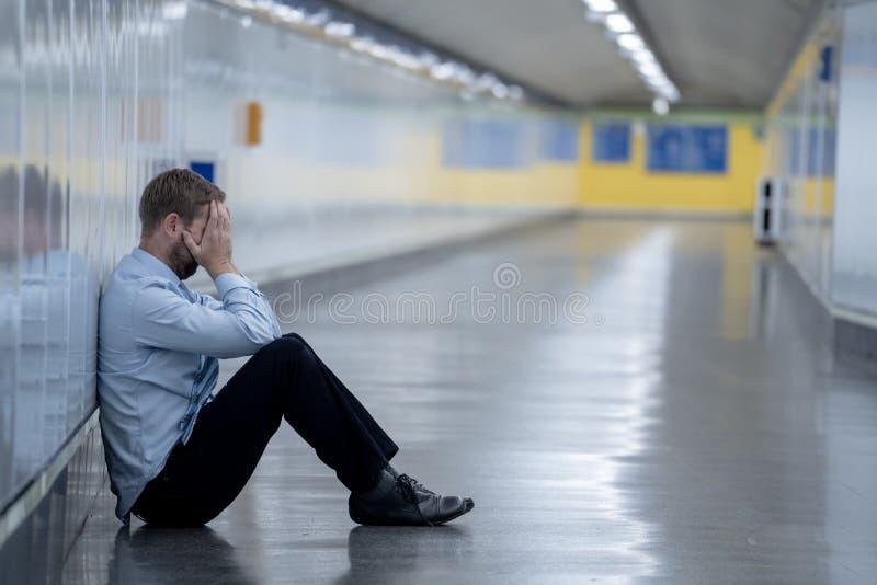 年轻失业的商人遭受的消沉坐倾斜在单独墙壁的地面街道地下看起来绝望  库存图片