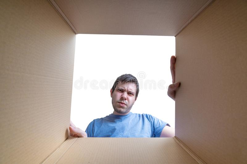 年轻失望的人在纸板箱里面的礼物看 免版税库存图片