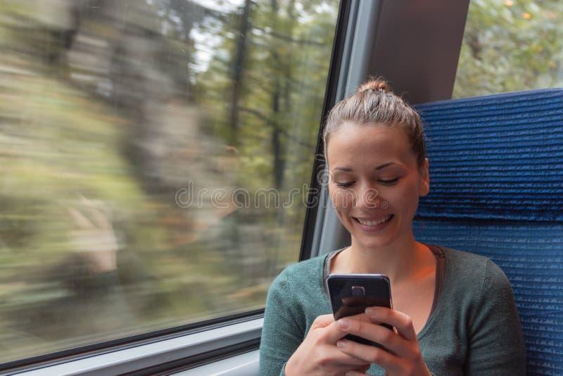 年轻女人与他的智能手机的正文消息在火车的一次旅途期间,当她工作时 免版税图库摄影