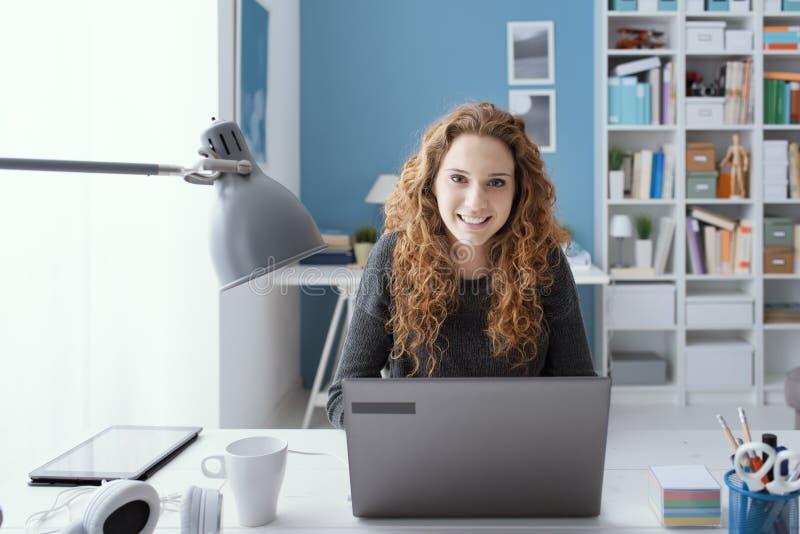 年轻女人与她的膝上型计算机一起使用 库存图片