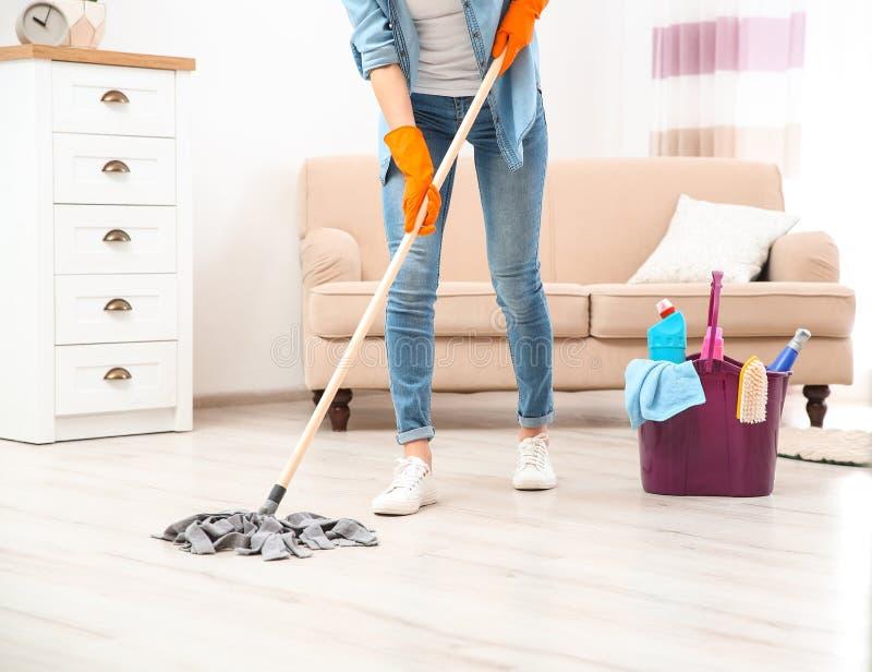 年轻女人与拖把的洗涤物地板在客厅,特写镜头 清洁 库存照片