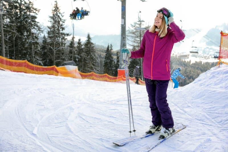 年轻女人与滑雪设备在山区度假村的消费寒假 库存照片