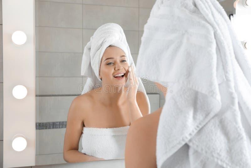 年轻女人与肥皂的洗涤物面孔在镜子附近 免版税库存图片