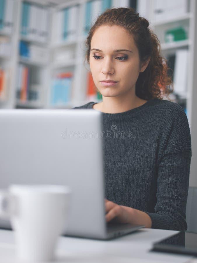 年轻女人与膝上型计算机一起使用 库存图片