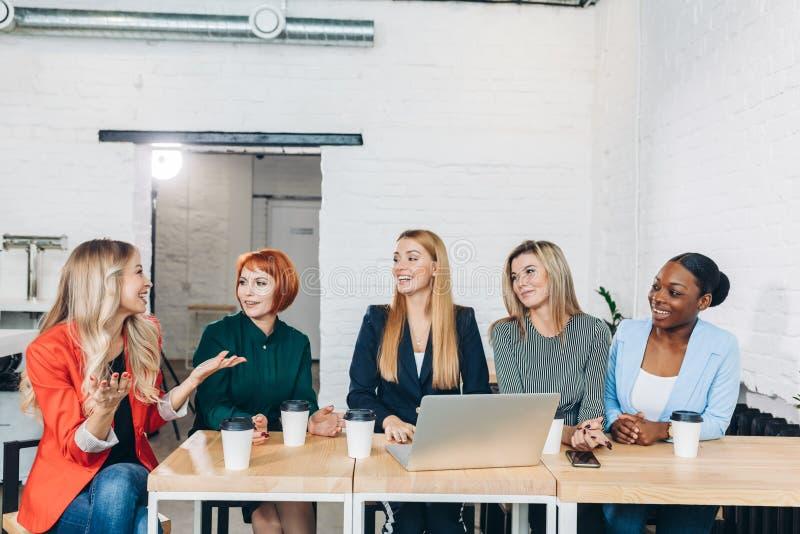 年轻女人与自由职业者的朋友合作并且创建一家小coworking的俱乐部 库存照片