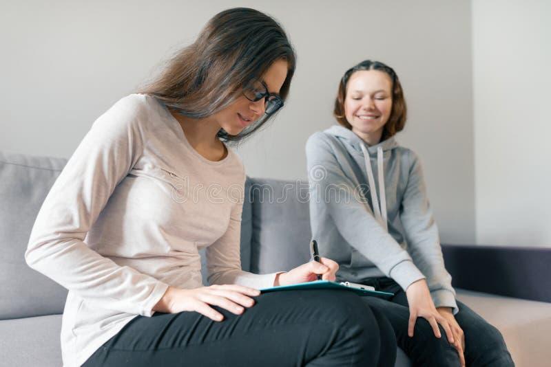 年轻女人专业心理学家谈话与少年女孩14,15岁在办公室坐沙发 精神健康  免版税图库摄影