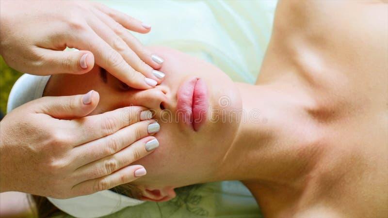 年轻女人享受在秀丽温泉沙龙的面部按摩在健康治疗 库存照片