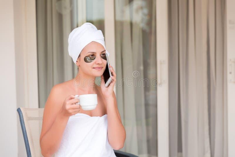 年轻女人以下眼睛补丁谈话由电话和饮用的咖啡在旅馆大阳台手段 免版税库存照片