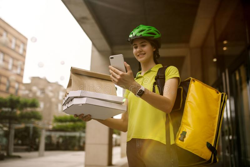 年轻女人作为运送比萨的传讯者使用小配件 库存图片