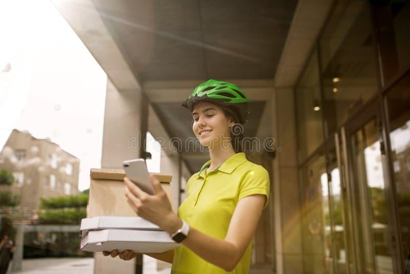 年轻女人作为运送比萨的传讯者使用小配件 库存照片