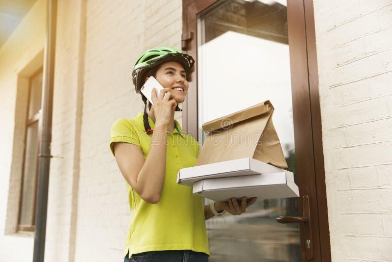 年轻女人作为运送比萨的传讯者使用小配件 免版税库存图片
