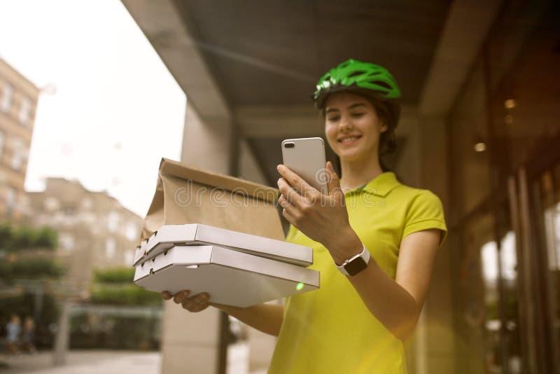 年轻女人作为运送比萨的传讯者使用小配件 免版税库存照片