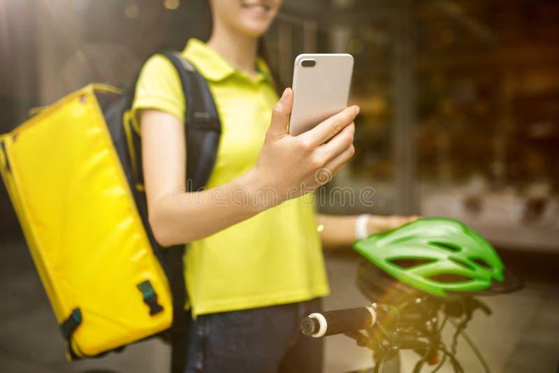 年轻女人作为运送食物的传讯者使用小配件 免版税库存图片