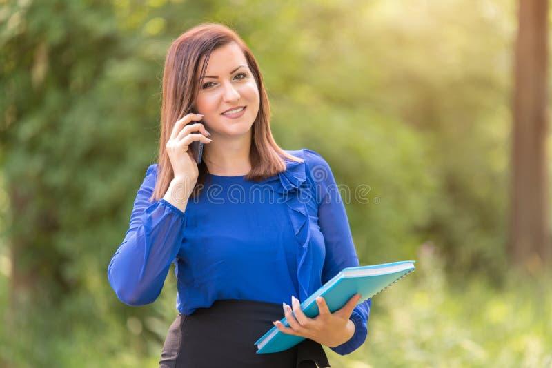 年轻女人使用她的电话和拿着一本蓝皮书 免版税库存图片