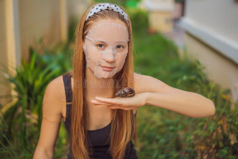 年轻女人做与蜗牛黏液的一面膜 爬行在面膜的蜗牛 库存照片