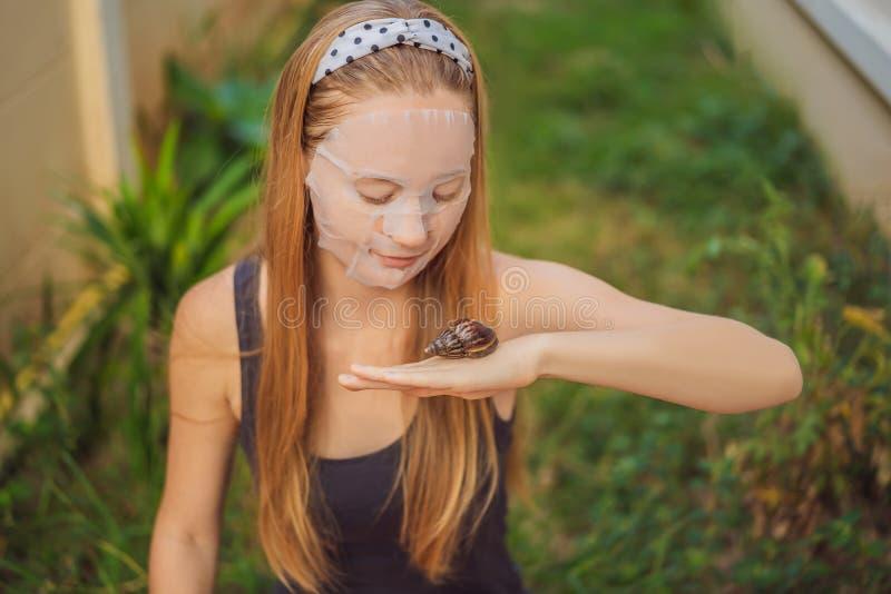 年轻女人做与蜗牛黏液的一面膜 爬行在面膜的蜗牛 免版税库存图片
