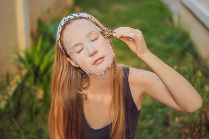 年轻女人做与蜗牛黏液的一面膜 爬行在面膜的蜗牛 免版税图库摄影