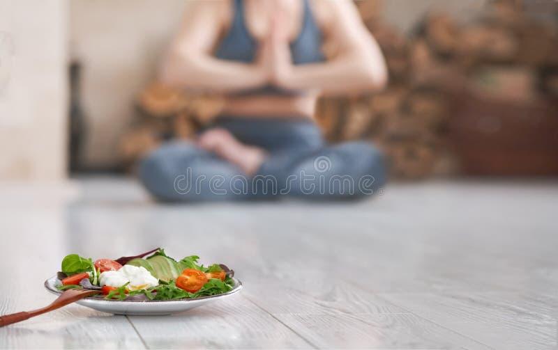 年轻女人做瑜伽 在锻炼以后的健康食品 免版税库存图片