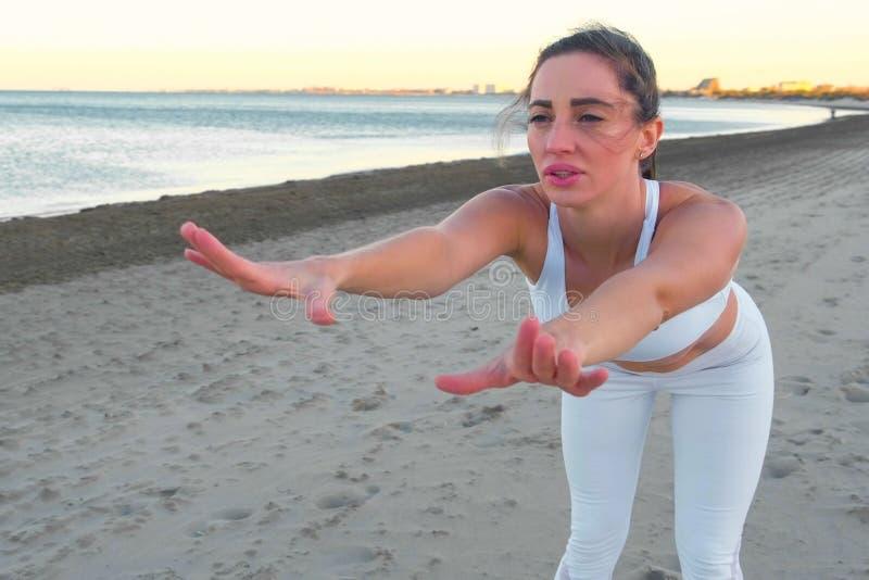 年轻女人做着在沙滩的瑜伽在日出 库存图片