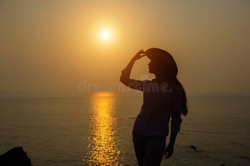 年轻女人剪影一个帽子的反对在海的日落 美丽的苗条女孩享受和平和放松在海洋 免版税库存照片