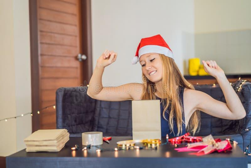 年轻女人包装礼物 在与红色和金丝带的工艺纸包裹的礼物圣诞节或新年 免版税库存照片