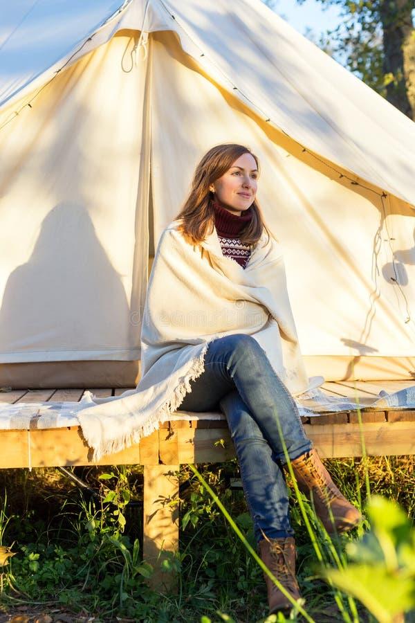 年轻女人包裹在她自己的一条毯子,当坐在帐篷附近时 免版税图库摄影