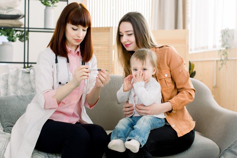 年轻女人医生测量的温度女婴孩子 采取婴孩的温度的医生 免版税库存图片