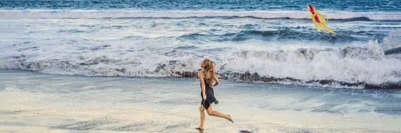 年轻女人发射在海滩的一只风筝 梦想,志向,未来规划横幅,长的格式 免版税库存照片