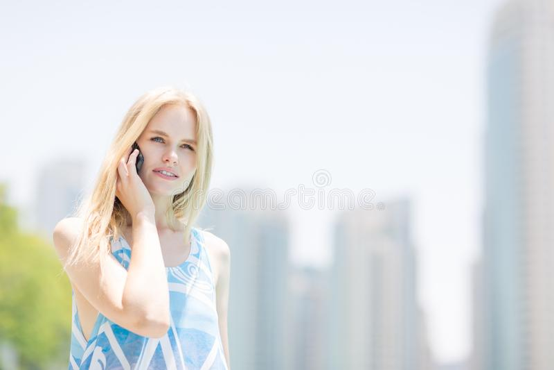 年轻女人发表演讲关于一个手机在城市 库存照片