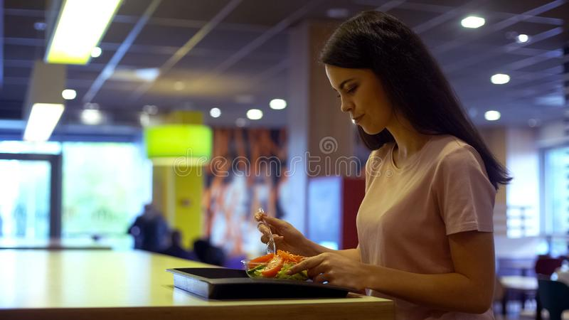 年轻女人吃午餐在军用餐具,吃菜沙拉坐的咖啡馆桌 图库摄影