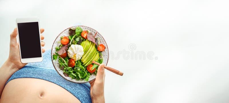 年轻女人吃沙拉并且在锻炼以后使用在她的智能手机的健身应用程序 免版税库存图片