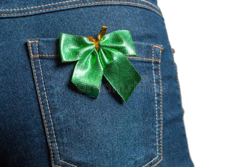 年轻女人后边牛仔布牛仔裤的 在后面口袋的绿色弓蝴蝶 困难光 查出的白色 免版税库存照片