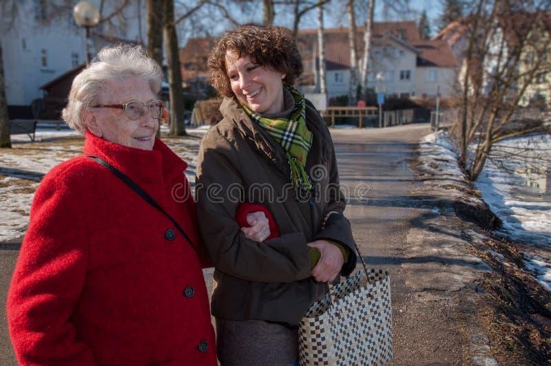年轻女人向购物与资深妇女求助 免版税库存图片