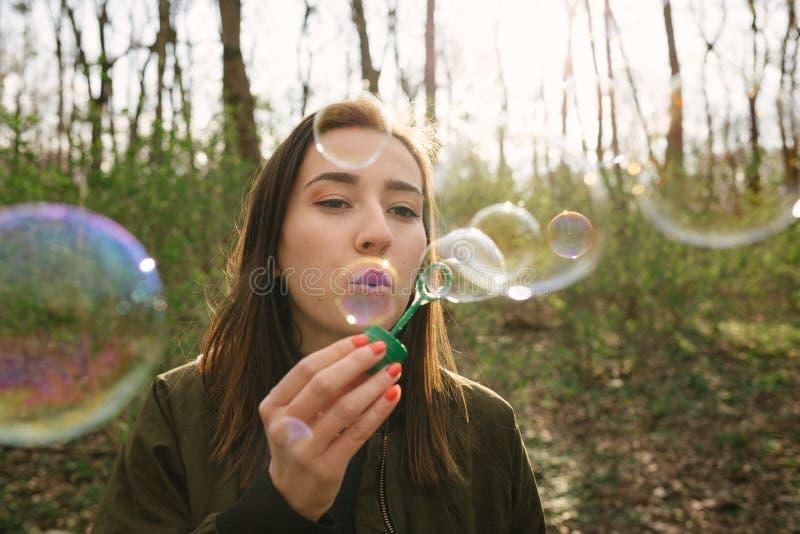 年轻女人吹的肥皂泡在森林 免版税库存照片