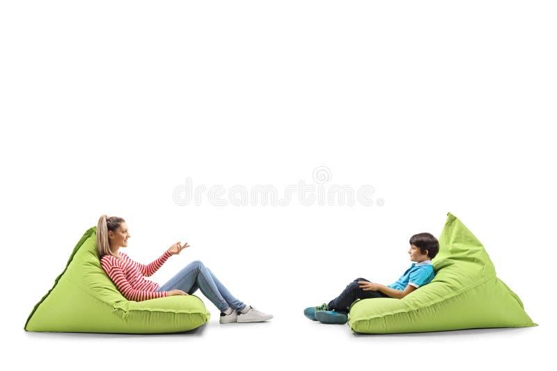 年轻女人和一名男孩坐有的辎重袋交谈 免版税库存照片