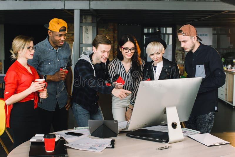 年轻女人和人自由职业者或者IT工作者使用膝上型计算机,观看在他们的工作 室内画象multiethnical 库存图片