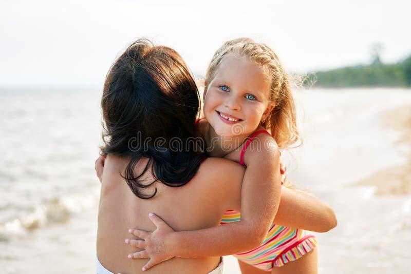 年轻女人和她的相当小女儿是拥抱和微笑在热带海滩 免版税库存照片