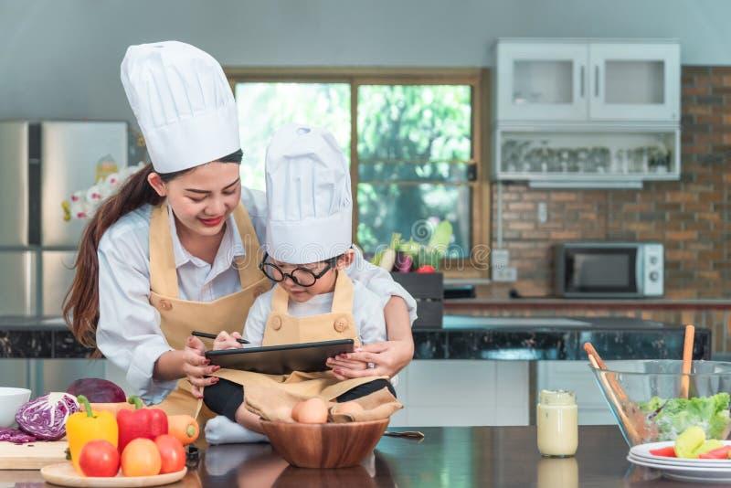 年轻女人和孩子使用片剂计算机,当烹调在厨房里时 Householding、鲜美食物和数字技术在生活方式 库存照片