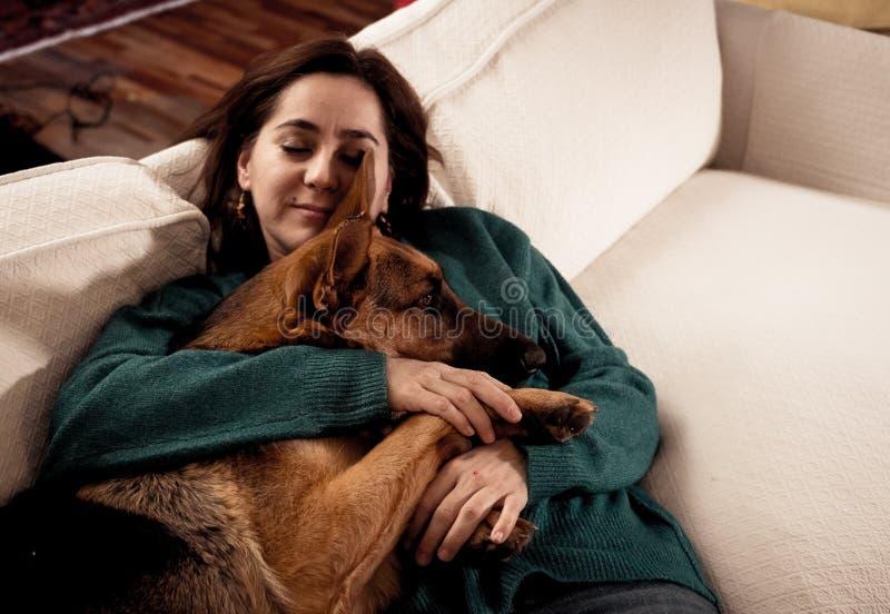年轻女人和狗拥抱在舒适家的德国牧羊犬逗人喜爱的画象在冬天 免版税库存照片