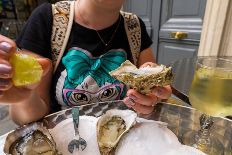 年轻女人品尝牡蛎用柠檬和一杯在街道咖啡馆的冷的白酒 免版税库存照片