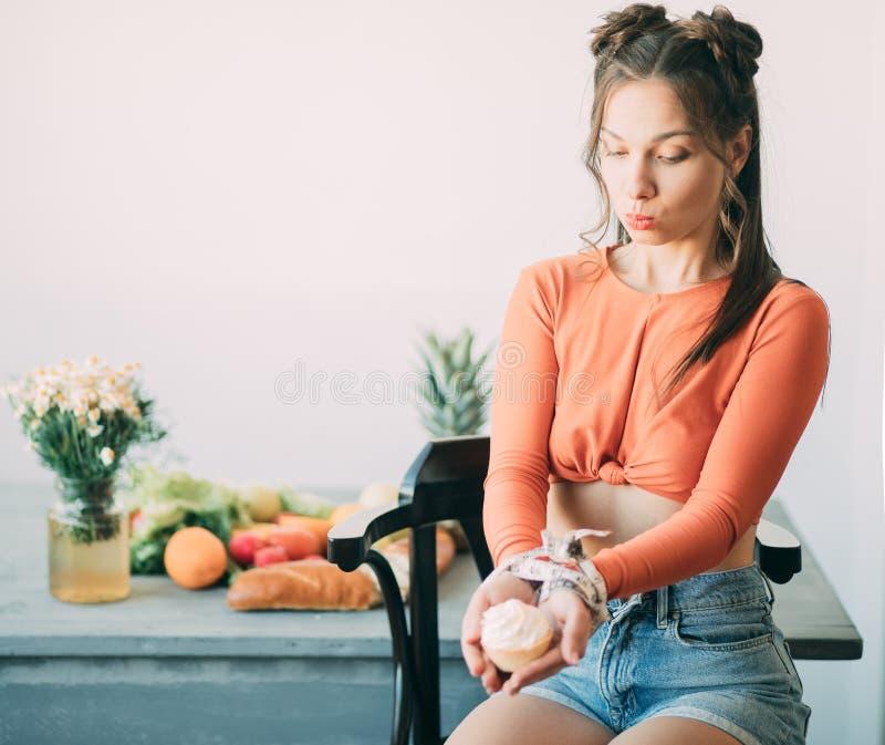 年轻女人在一卷测量的磁带一定的她的手上拿着一个蛋糕在桌上的健康食品旁边 免版税库存图片