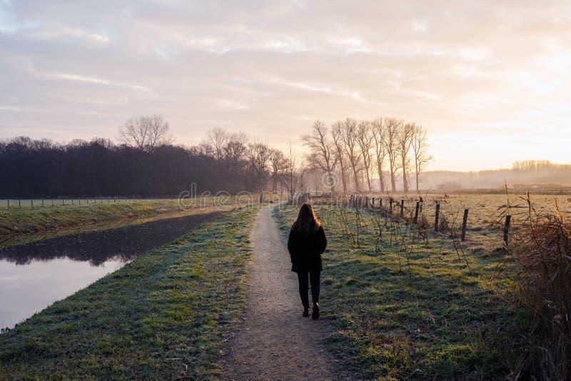 年轻女人在一寒冷走由日落的,五颜六色美好的风景的背景河 免版税库存照片