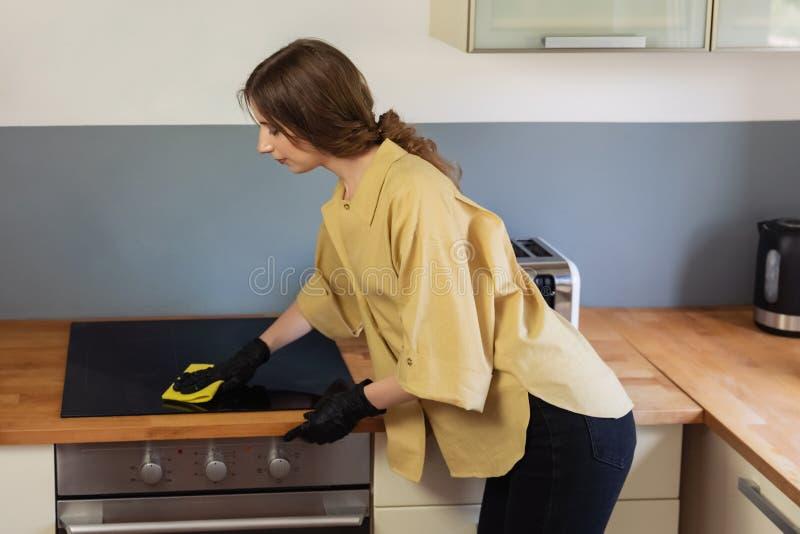 年轻女人在厨房,洗碗里清扫 免版税库存图片