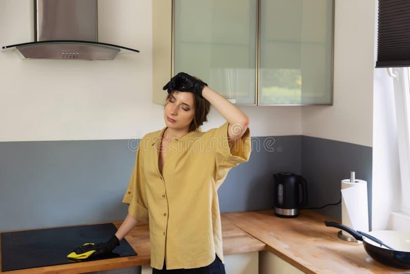 年轻女人在厨房,洗碗里清扫 免版税图库摄影