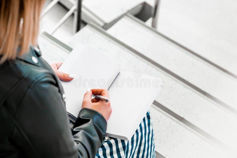 年轻女人在图书馆做在紫罗兰色笔记薄的笔记和坐梯子步 库存照片