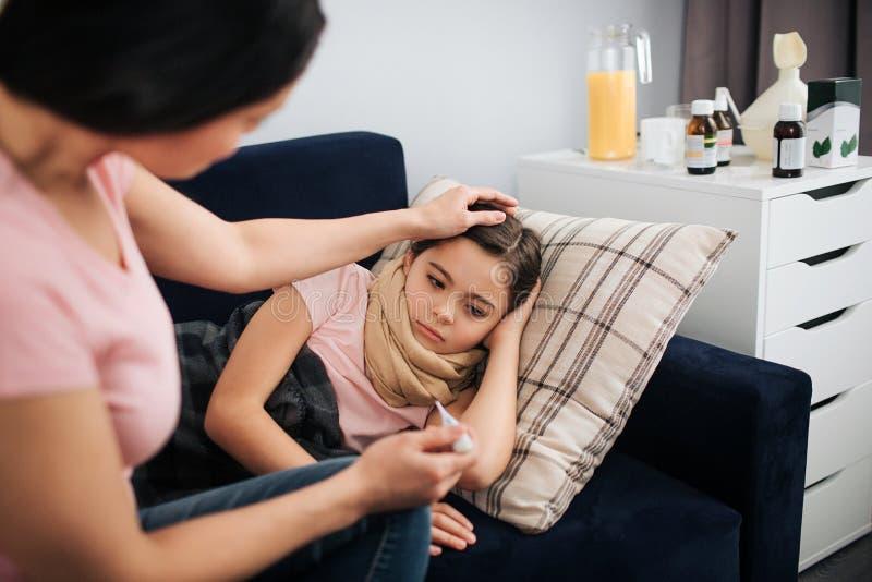 年轻女人在她的女儿的长沙发旁边坐 她接触她的头发和前额 妇女举行温度计在手中 哀伤和 库存照片
