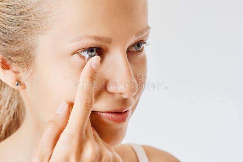 年轻女人在她的眼睛投入隐形 Eyewear、眼力和视觉、眼睛关心和健康、眼科学和视力测定概念, 库存图片