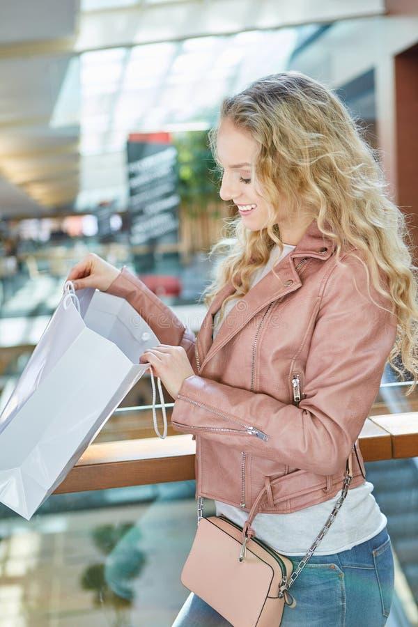 年轻女人在她的食品杂货袋看 库存图片