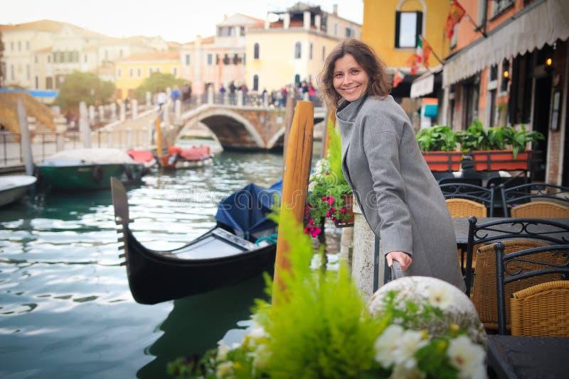 年轻女人在威尼斯,意大利 女孩在长平底船和街道运河背景的威尼斯 免版税库存照片