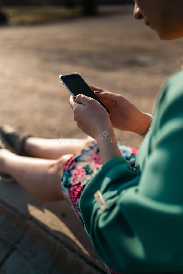 年轻女人在宫殿公园使用电话坐喷泉-关闭  免版税库存照片